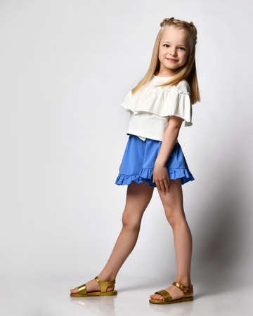 cute smiling little girl in white blouse, shorts and sandals isolated on white background