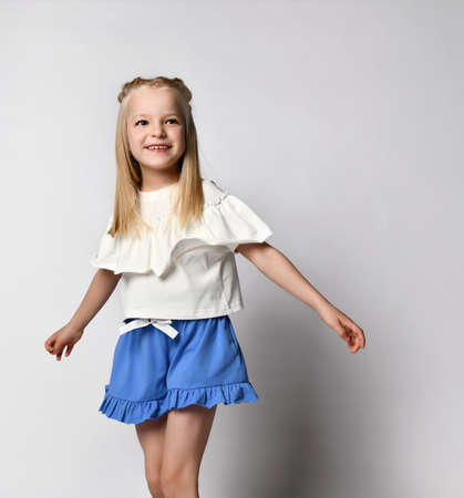 cute smiling little girl in yellow shirt, shorts and gumshoes isolated on white background Standard-Bild
