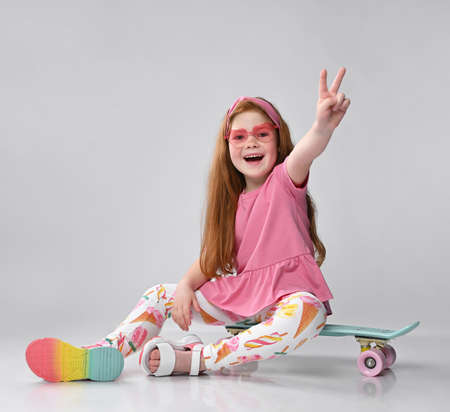 Smiling little red-haired girl child sitting on skateboard gesturing victory