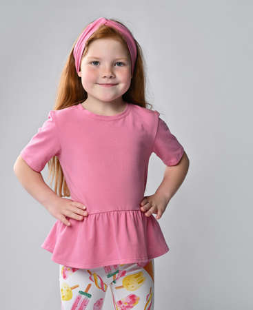 Smiling little red-haired girl child turning from back looking at camera