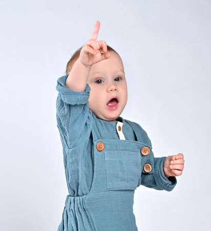 indignant todler todler in a blue jumpsuit raised his hand with a middle finger up, calling for the attention of his parents Standard-Bild