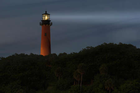 Lighthouse light beam at night photo