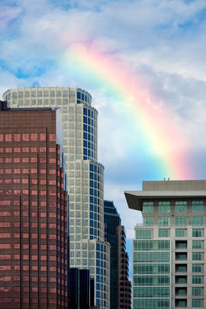 A shot of high rise buildings in downtown Los angeles under rainbow and cloudy blue sky photo