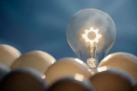 Solution and communication business concepts  Idea symbol, light bulb, gear inside light blob  photo