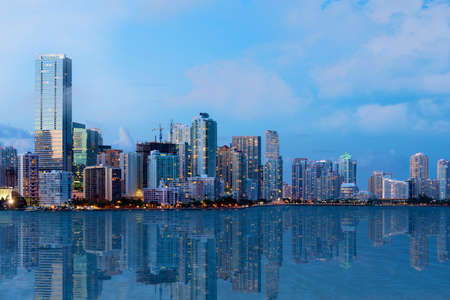 A shot of beautiful Downtown Miami skyline after sunset with reflection in the water  All logos and advertising removed