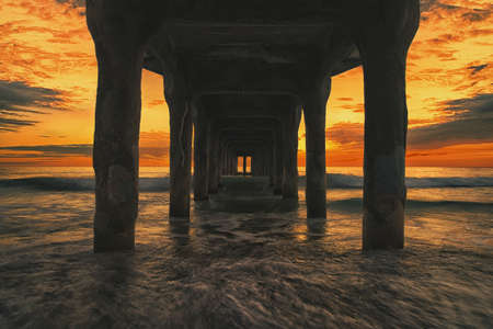 Pier at Manhattan Beach in Los Angeles, California, United States lit by a stunning sunset