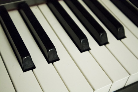 Acoustic piano black and white keys in close zoom. Stock Photo