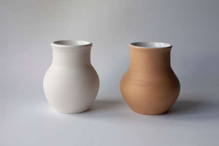 Two ceramic milk pots of white and terracotta clay. Rustic style.