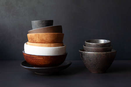 Still life with handmade ceramic dishware on a black background. Plates, bowls, pialas. Rustic style. 免版税图像