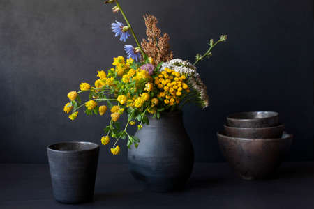 Still life with handmade ceramic dishware and field flowers in a black vase. Rustic style.