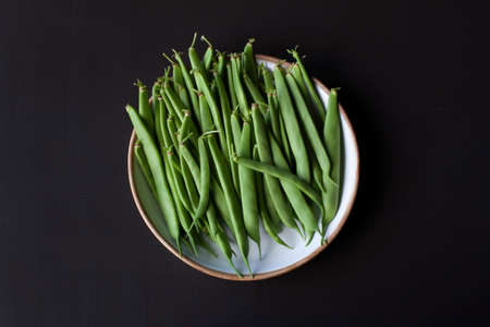 Green beans on a handmade ceramic plate isolated on black background. Top view.