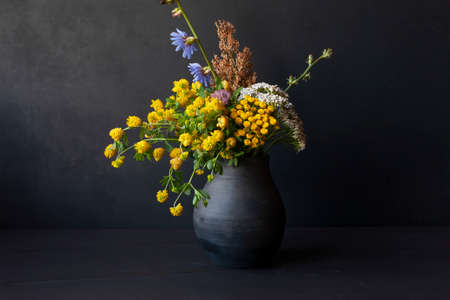 Bouquet of wild flowers in black handmade ceramic vase. Rustic style. 免版税图像