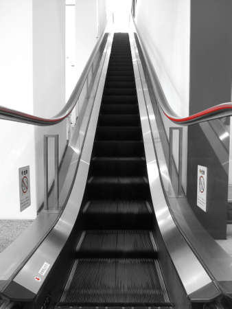 escalator with red hand rails and glass sides