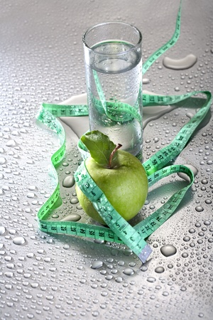 Healthy concept - apple glass of water and tape photo