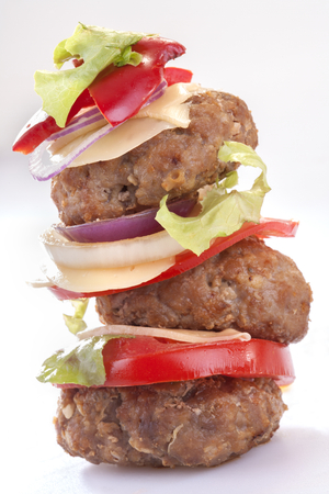 hamburgers with cheese, onion, tomato and lettuce photo