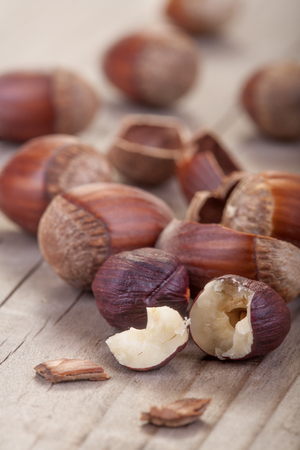 hazelnuts with its shell on a wooden table photo