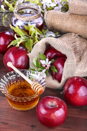 apples in a linen bag with honey and apple flower on wooden table photo
