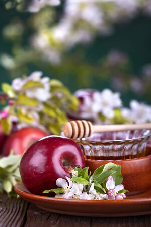 apples in a bowl with honey and apple flower on wooden table photo
