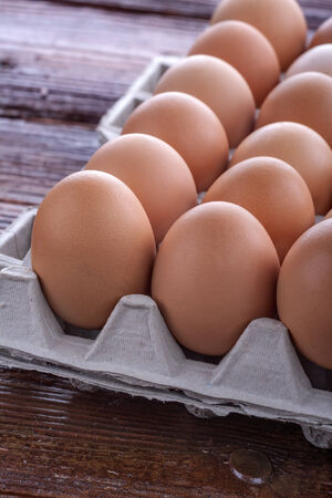 eggs arranged in a cardboard on a wooden table photo