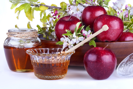 apples in a bowl with honey and apple flower on a white background photo