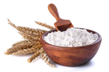 meel met tarwe in een houten kom en schep op een witte achtergrond