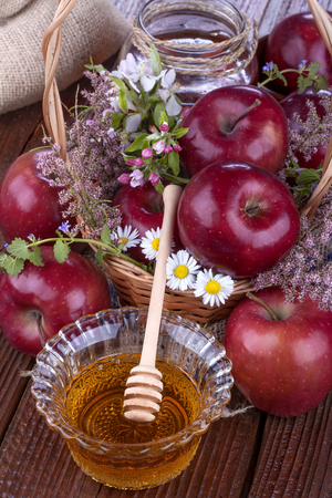 apples in a basket with honey and flowers on wooden table Standard-Bild