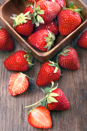 healthily: healthily raised organic strawberries in a wooden bowl on the table