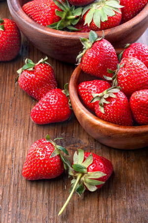 healthily: healthily raised organic strawberries in a wooden bowls on the table