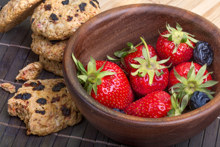 Cakes of healthy cereal with dried fruits and fresh strawberries photo