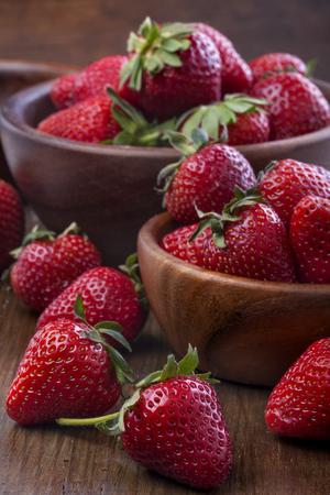 healthily raised organic strawberries in a wooden bowls on the table