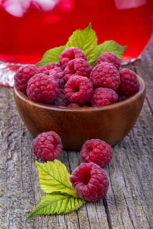 Healthy organic raspberries on an old rustic table with juice in the background photo