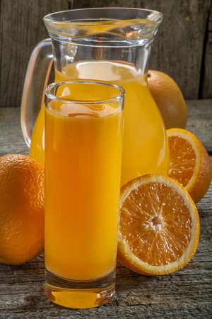 A refreshing orange juice on rustic wooden background photo