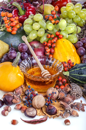 Autumn fruits, nuts and vegetables with honey on white