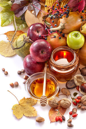 Honey, apples and autumn fruits on the white background photo