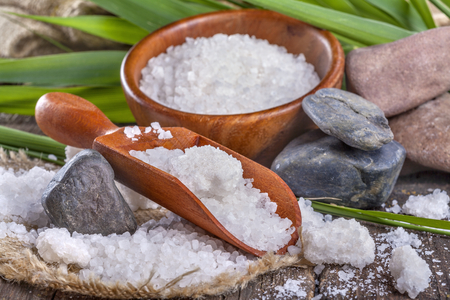 salt bath in wooden bowl with bamboo leaves in background