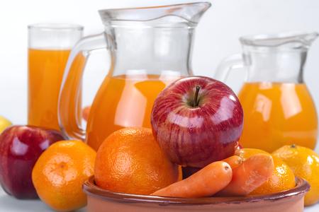 verre de jus d orange: pomme, orange et carottes avec jus de fruits frais dans le fond