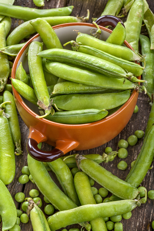 sweet sugar snap: peas in pods in ceramic bowl on a wooden table Stock Photo