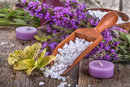 bath salts: salt bath in wooden spoon with flowers and  leaves in background Stock Photo