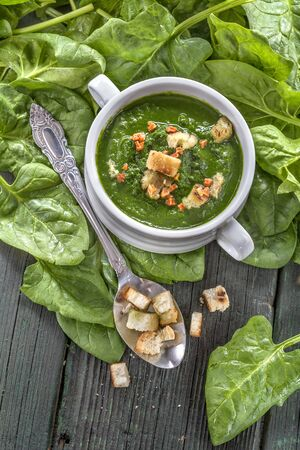 potage: Spinach potage cream soup in bowl on rustic table