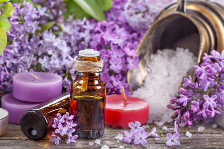 Essential oils and bath salt with a background of lilac Standard-Bild