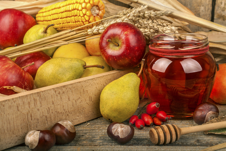 Honey with autumn fruits on a rustic surface