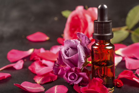 Essential oil with rose flowers and petals on black  background. Aromatherapy spa herbal natural medicine products