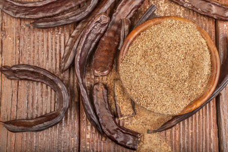 Carob pods and carob powder in a bowl on rustic background
