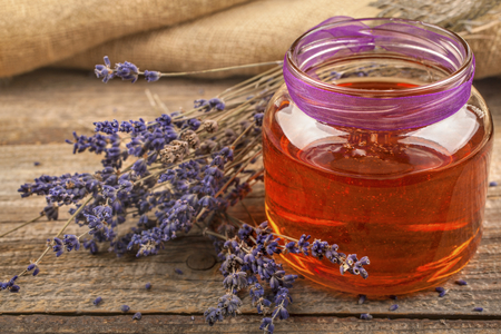 Honey from lavender with a lavender flower on a rustic background