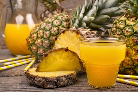 Freshly squeezed juice of pineapple on a rustic background Archivio Fotografico - 129485313