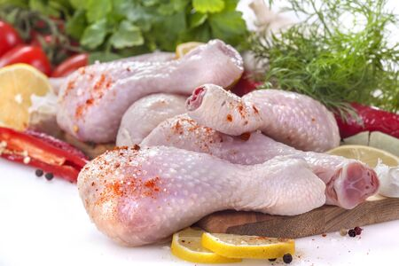 Fresh chicken legs with tomatoes, lemon and spices, on a white background