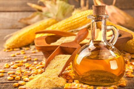 Healthy homemade organic corn oil on rustic wooden table
