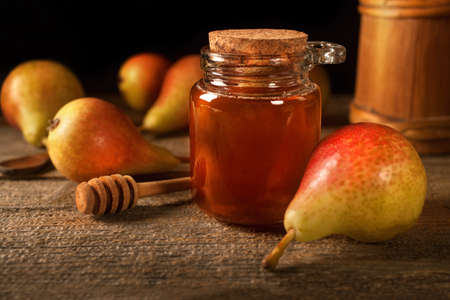 Ripe organic pears with honey on the wooden rustic board. The concept of healthy eating and nutrition. Vintage style composition.