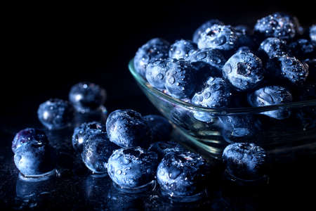 Freshly picked blueberries in a glass jar. Fresh and healthy juicy blueberries on a dark background. Blueberries as a fruit antioxidant symbol. Concept for healthy eating and nutrition. Standard-Bild