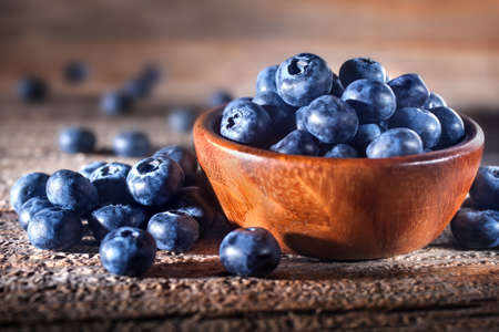 Freshly picked blueberries in a bowl. Fresh and healthy juicy blueberries on a rustic background. Blueberries as a fruit antioxidant symbol. Concept for healthy eating and nutrition. Standard-Bild
